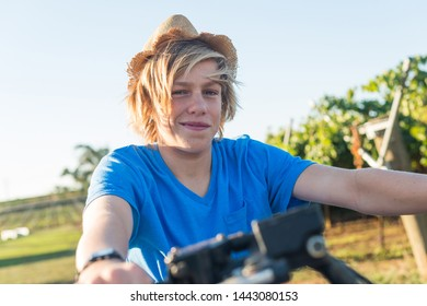Happy blond guy in straw hat and and blue t-shirt sitting on bike. Teenager riding quad bike on background of vine rows. Traditional farming in vineyard. Summertime activity countryside.