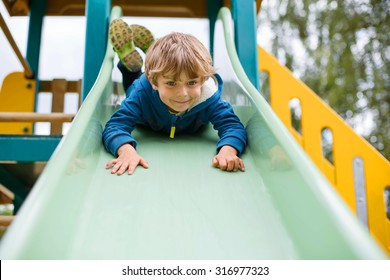 Happy blond kid boy having fun and sliding on outdoor playground. Child smiling. Summer leisure for kids.