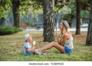 happy blond mom with her little son enjoying nature on a background of green leaves.
