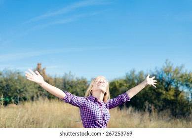 Happy blond pretty girl having fun standing in the field hands up on blue sky copy space background