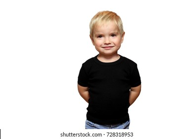 Happy blond toddler boy in black t-shirt without any logo over white background, hands behind the back, isolated, emotional child portrait, closeup indoor, place for your text