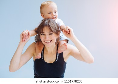 Happy blond toddler boy laughing on to his sportive mother for a piggyback ride over gray background. Close up portrait. Fitness, happy maternity yoga with children concept.