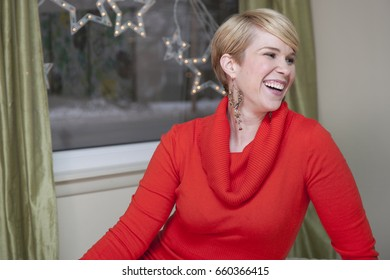 Happy blond woman laughing, Christmas star light decoration hanging from window in background.
