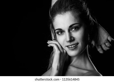 happy blond woman on black background with copy space looking at camera, monochrome