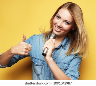 Happy blond  woman singing in microphone over yellow background