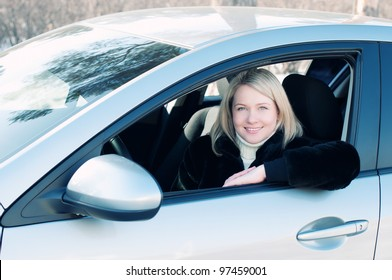 Happy blond woman sitting in her car outdoors, smiling and looking at camera