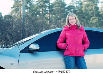 Happy blond woman standing by the automobile outdoors