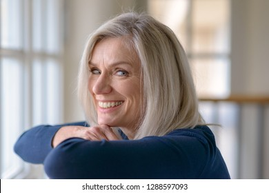 Happy blond woman with a vivacious friendly smile turning to glance at the camera as she leans on a bannister in front of a large window