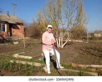 Happy blond woman in white trousers, pink jacket and white cap is working at the dacha. Spring landscape