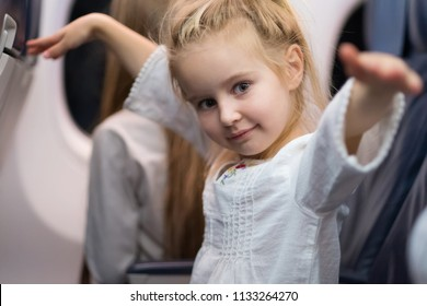 Happy blond young girl in white blouse travelling by plane.