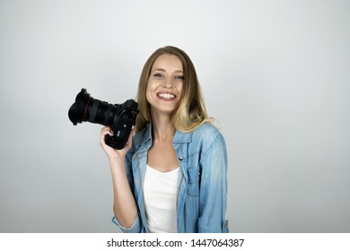 happy blond young woman holding photocamera in her hand smiling isolated white background
