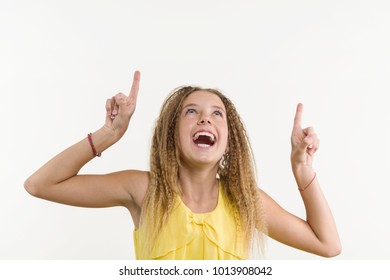 Happy blonde with curly hair, teen girl pointing her index finger up, indicating copy space on white blank wall for your content or information information