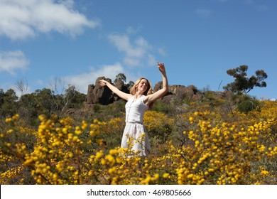 happy blonde girl, dancing in a field full of yellow flowers. background of summertime and blue skies.