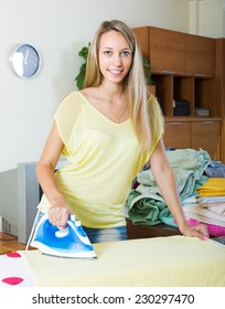 Happy blonde girl ironing with iron and ironing board at home