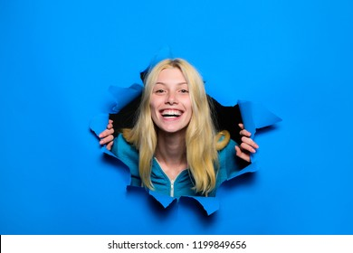 Happy blonde girl looking through hole in paper. Woman breaking through paper wall. Emotions. Emotional woman breaking through paper. Season sales. Discount, sale. Black friday shopping. Advertising.