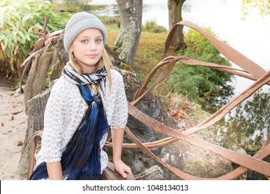 Happy blonde girl outside sitting on river bench park