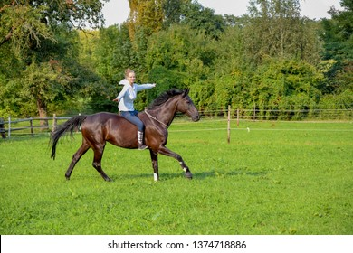happy, blonde girl riding black horse in a green field in canter without saddle and bridle building trust between horse and rider with natural horsemanship and free dressage exercises