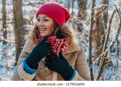 Happy blonde girl in a snowy winter forest with sunset light