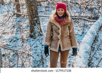 Happy blonde girl in warm clothes inside snowy winter forest with sunset light