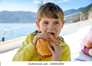 Happy blonde kid boy enjoying sailing boat trip. Family vacations on ocean or sea on sunny day. Healthy beautiful school child eating big sandwich with salami. Coastline with villages and nature
