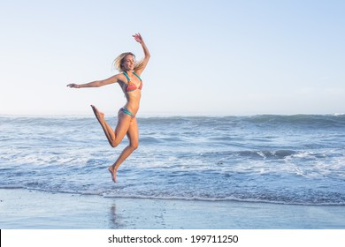 Happy blonde leaping on the beach in bikini on a sunny day