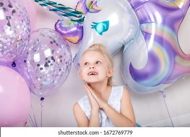 Happy blonde little girl with a  big helium balloon unicorn