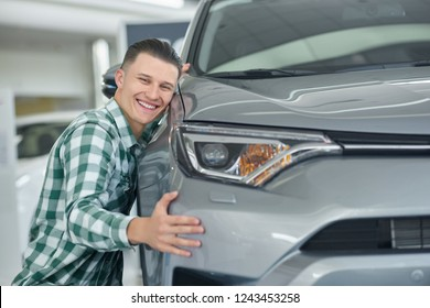 Happy blonde man smiling after buying his first car. Attractive young client choosing auto and squatting near it. Handsome owner in checkered shirt really liking his vehicle and hugging it.