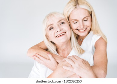 happy blonde mature daughter and senior mother in total white outfits embracing isolated on grey