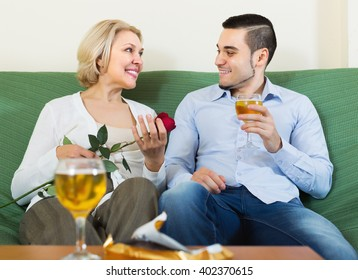 Happy blonde mature woman chatting with young smiling boyfriend indoors