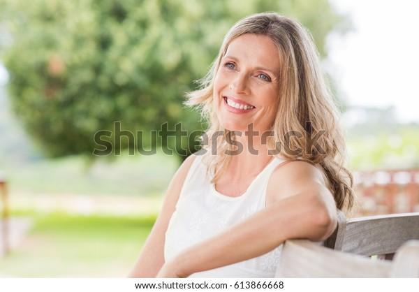 Mulher madura loira feliz sentada ao ar livre e pensando. Mulher sênior relaxando em um banco de madeira sob a árvore em um dia de verão. Retrato de mulher de meia-idade sorrindo e sonhando acordado.