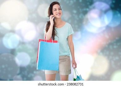 Happy blonde with shopping bags on the phone against blurred lights