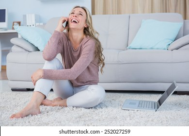 Happy blonde sitting on carpet phoning at home in the living room