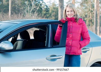 Happy blonde standing by the car outdoors and looking at camera