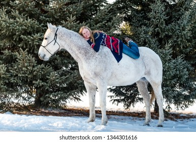 happy blonde teenager girl bareback on her white/grey handsome horse. background of snow and pine trees