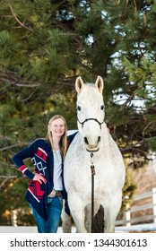 happy blonde teenager girl holding white/grey handsome horse.
