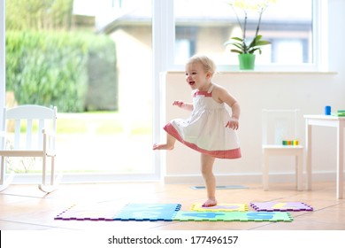 Happy blonde toddler girl having fun dancing indoors in a sunny white room at home or kindergarten