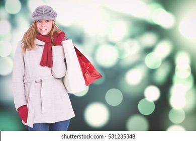 Happy blonde in winter clothes with bags against light circles on green background