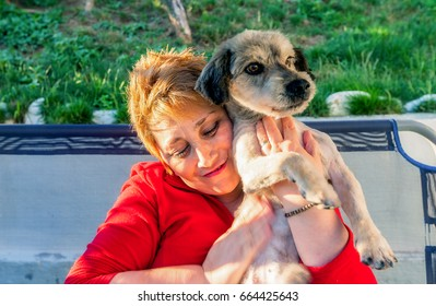 Happy Blonde Woman Clutching At Chest Newly Adopted Terrier Dog