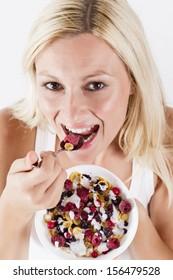 Happy blonde woman eating muesli with fruit at breakfast.