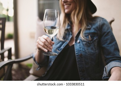 happy blonde woman enjoying white wine and smiling