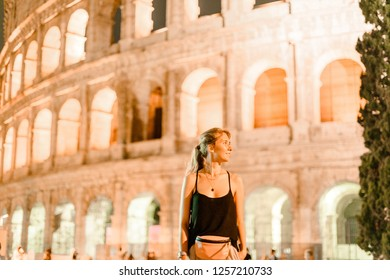 Happy blonde woman girl in black shirt with pink waist bag smiling in front of Rome Colloseum
