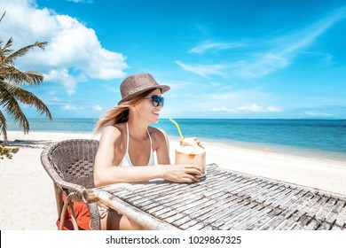 Happy blonde woman in hat and sunglasses on the tropical beach sitting in cafe with coconut