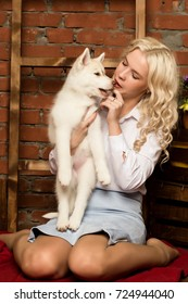 happy blonde woman with husky puppy on a autumn harvest background