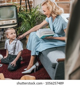 happy blonde woman reading book and looking at cute little son playing on carpet at home, 1950s style family