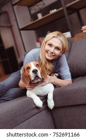 happy blonde woman smiling at camera while lying on sofa with dog