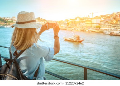 Happy blonde woman - tourist shot on her smartphone camera beautiful city view. with ships on the river in sunny day.