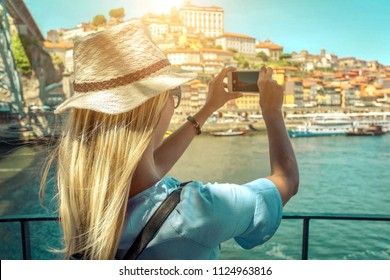 Happy blonde woman - tourist shot on her smartphone camera beautiful city view with ships on the river in sunny day.