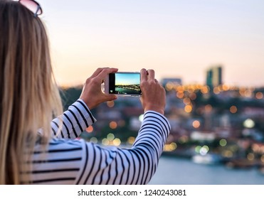 Happy blonde woman - tourist shot on her smartphone camera beautiful city view with bokeh, on the river in sunny day.