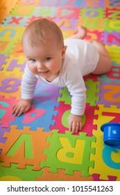 Happy blue-eyed baby learning to crawl on bright alphabet mat.