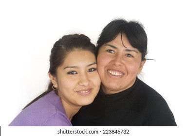 Happy Bolivian woman with her teenager daughter embracing each other and smiling. White background.